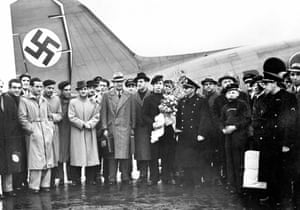 A football team assembled on the apron in front of a newly-painted swastika tail fin.