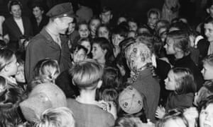 A group of Berlin children crowd around Lieutenant Gail Halvorsen, the originator of Operation Little Vittles for the thousands of packages of sweets he dropped over Berlin in tiny parachutes in1949.