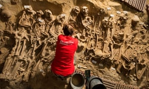 An archaeologists at works at the site of eight mass graves found under a store in Paris