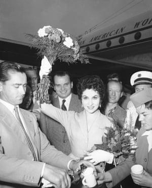 Italian screen star Gina Lollobrigida and her husband, doctor Mirko Skofic (left) pouring drinks upon their arrival at Tempelhof for Berlin's fourth international film festival, 1954.