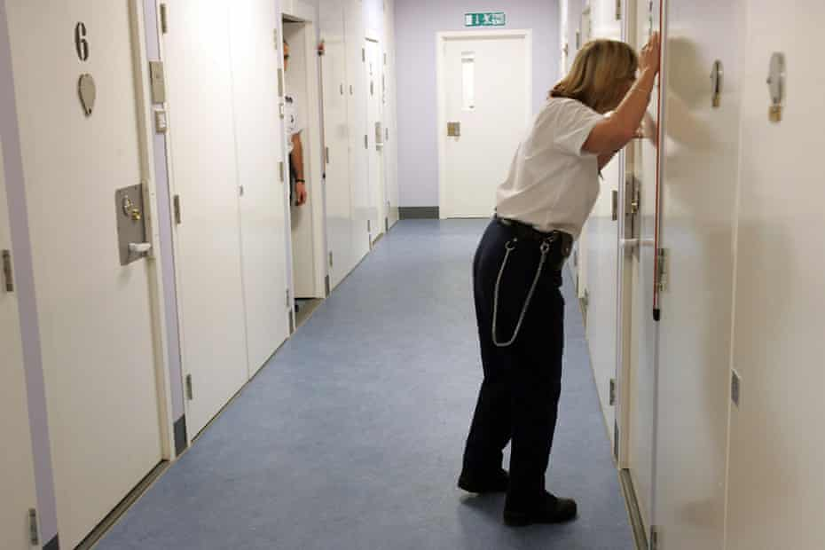 A detention officer looking through a cell door observation hole, at the Colnbrook immigration removal centre at Heathrow Airport, where staff are struggling to cope with soaring numbers of dangerous and vulnerable detainees
