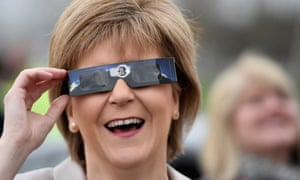 First Minister Nicola Sturgeon uses protective glasses to look into the sky at a partial solar eclipse in Glasgow, Scotland.