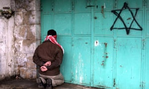 A blindfolded and handcuffed Palestinian kneels against a door with a spray-painted Star of David, after he was arrested by Israelis in January 2006, in the West Bank town of Hebron.