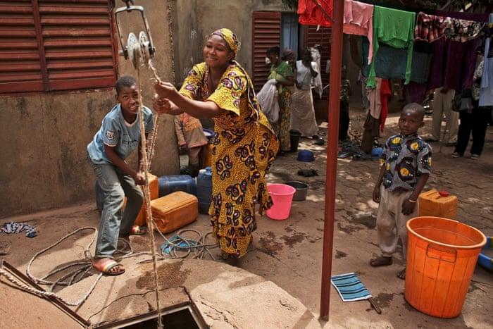 Sally Cisse, right and and neighbour Mamadou Coulibaly, pull up unclean water from a deep well in the courtyard of a compound in Kalabancoro, a town on the outskirts of Bamako. Population growth and increasing urbanisation in many parts of Africa are creating more challenges. Many countries do not have the systems for dealing with growing towns. Instead they are often using approaches adapted from rural areas<br>