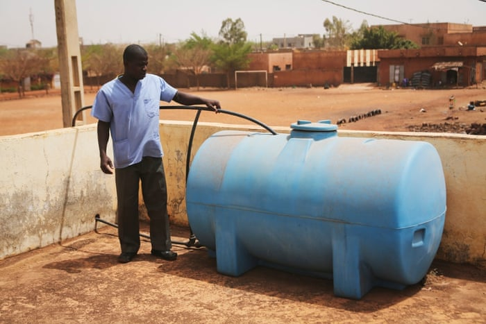 Emmanuel Coulibaly shows the tank that holds water on the top of the nearby community health centre. The clinic relies upon a traditional well which is covered over. By pumping the water to the roof, it can then be piped into sinks in the delivery room. Staff must either buy safe drinking water or ask nearby households and patients to bring it in. Mariame Wallett Mohammed, 22, is pregnant with her first child. 'It costs us 500 to 600 CFA to buy water (just under a dollar), more if we have guests or for washing,' she says