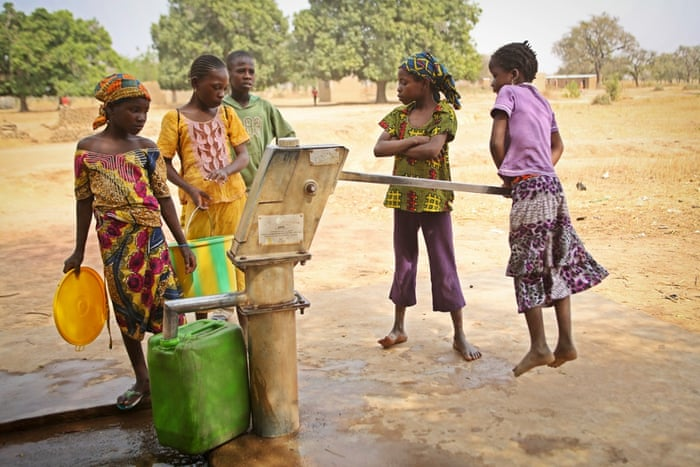 "Fanta Diarra, 6, right, takes her turn to pump clean water from the borehole. Rwanda is one of the few African countries projected to meet the millennium development goal target on water and sanitation. Target 7.C is to halve, by 2015, the proportion of the population without sustainable access to safe drinking water and basic sanitation. Water and sanitation is the <a href=""http://www.theguardian.com/global-development/2014/nov/19/water-sanitation-target-development-goals-un"">least on track</a> of the 21 targets"
