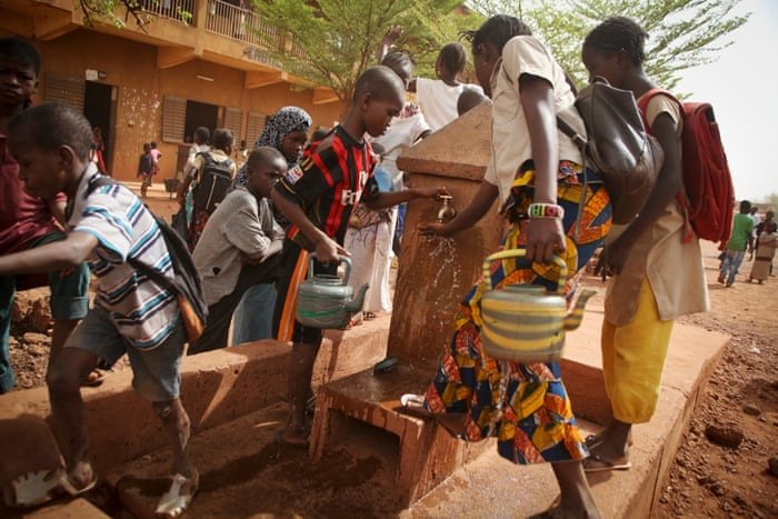 Students fill containers at a water point during a break in classes at a school in the Sabalibougou area of Bamako. WaterAid installed a water point at this school in 2006 which has 4,500 students from years 1 to 9