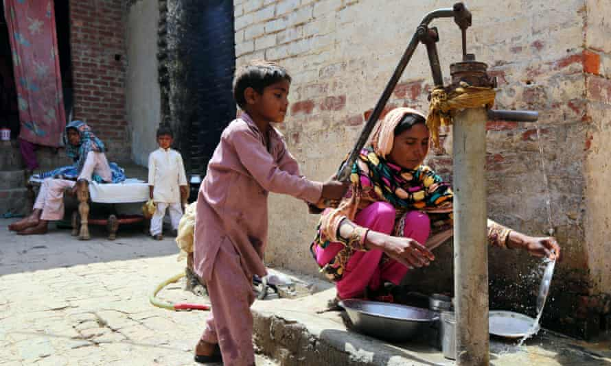 Boy pumping water outside a house in Lahore, Pakistan.