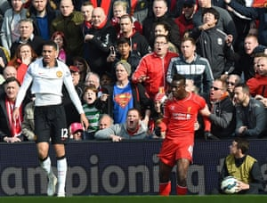 Mario Balotelli is held back by supporters after a clash with Chris Smalling.