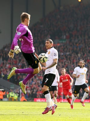 Angel di Maria and Simon Mignolet challenge for the ball.