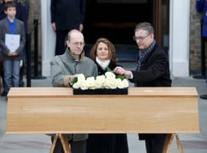 Canadian-born carpenter Michael Ibsen, left, the King's 17th great-grandnephew, places a rose on the oak coffin.