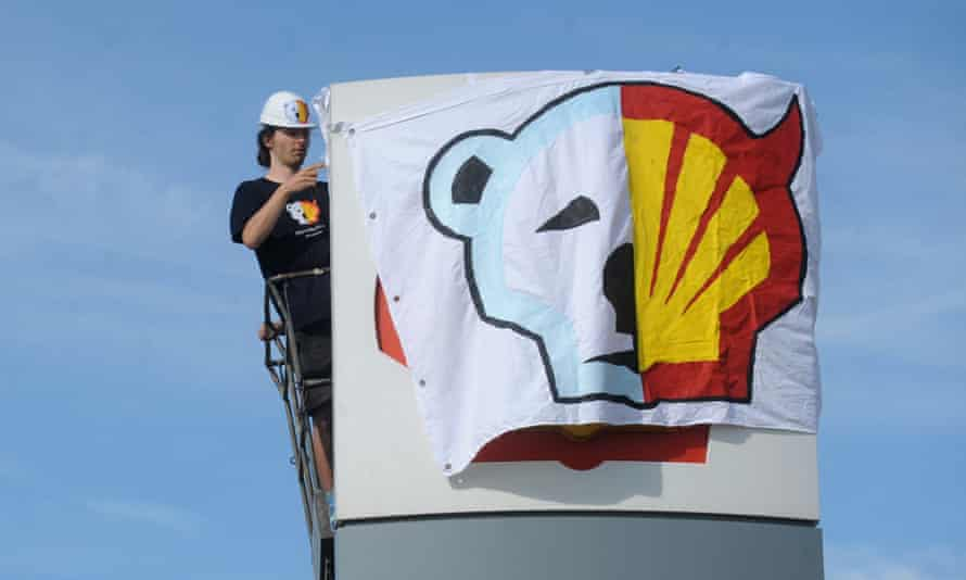 A Greenpeace activist covers the logo of the Shell oil company to protest against the heading of the an icebreaker for Shell's Arctic oil drilling project in the north of Alaska in 2012.