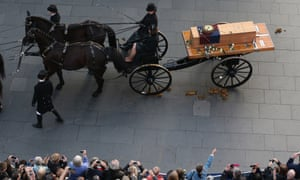 People throw white roses on the coffin containing the remains of King Richard III as it is carried into Leicester cathedral.