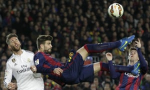 Gerard Piqué almost takes off the head of his Barcelona team-mate Lionel Messi as he beats Real Madrid's Sergio Ramos to the ball.