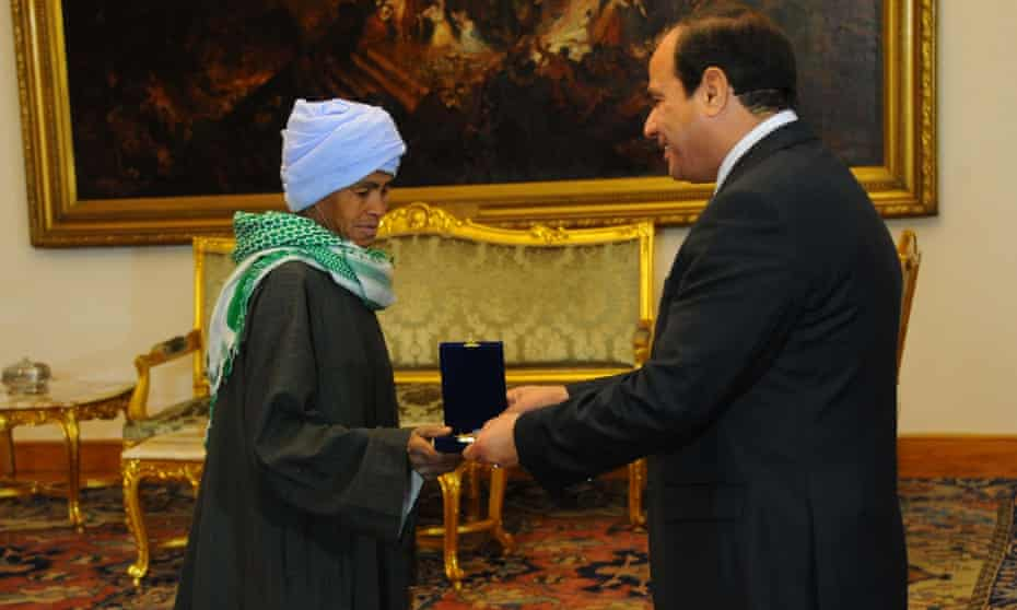 Egypt's president, Abdel Fatah al-Sisi, hands Sisa Abu Daooh the motherhood award