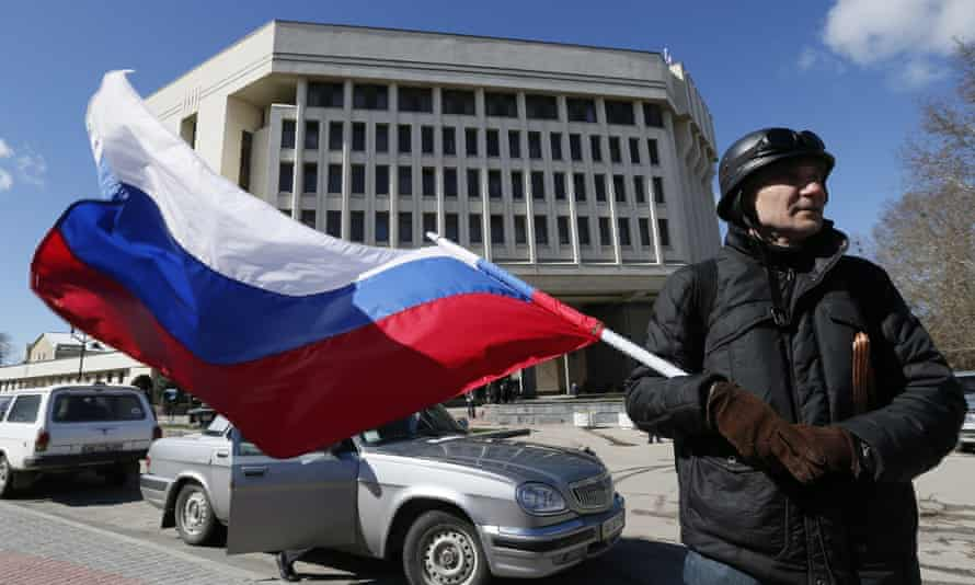 A man holds a Russian flag as he stands in front of the Crimea's parliament in Simferopol, Crimea. The head of the Duma's foreign affairs committee said Russia has more right to Crimea that Britain to the Falkland Islands