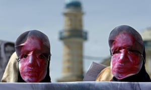 Afghans wear masks during a protest to condemn the killing of 27-year-old Farkhunda, who was beaten with sticks and set on fire by a crowd in Kabul on Thursday.