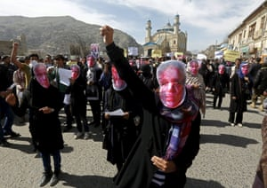 Supporters of the Hambastagi party (Solidarity party of Afghanistan) wear masks during a protest to condemn the killing of Farkhunda, a 27-year-old woman who was beaten and set on fire by men in central Kabul on Thursday