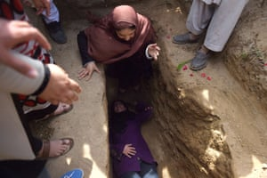 Women weep and lie on Farkhunda's grave