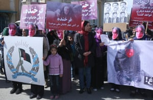 Women wear masks and hold graphic pictures of  Farkhunda, during a protest by the Solidarity Party of Afghanistan at the site of the attack in Kabul