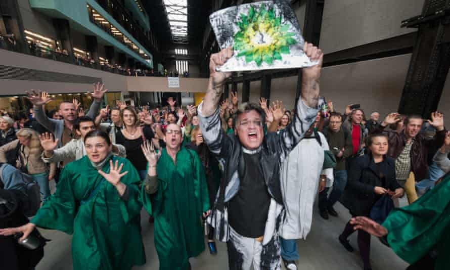 Reverend Billy leads the congregation out of Tate Modern holding up an oil-soaked BP logo. -- The Reverend Billy performed at Tate Modern today, urging an end to extraction of oil for the Tar Sands and of arts sponsorship by BP, which gives a company engaged in this most polluting activity a false green image. London, UK. 18th July 2011