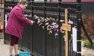 A woman ties prayer ribbons to Leicester Cathedral fence