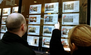 Couple looking in estate agents window