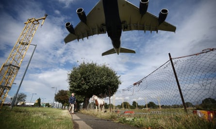 A passenger plane comes into land over a field containing horses near Heathrow.