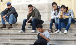 Some of Tunisia's more than 600,000 unemployed, almost half of whom are graduates from higher education institutions, sit on the steps of a theatre on Tunis's Habib Bourguiba Avenue.