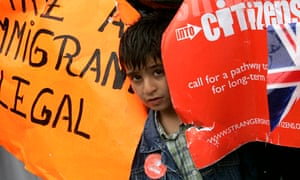 A child peers out during the migrant's day march for immigrant rights in Trafalgar Square
