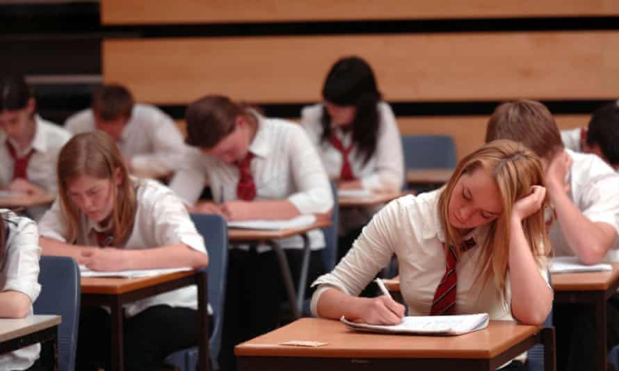 British school pupils in exam conditions in a school hall.