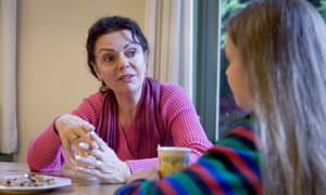 Teenager girl and mother talking seriously at dinner table