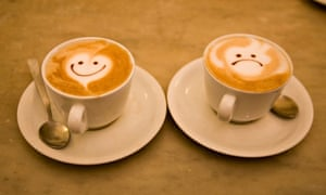 Face designs on cups of cappuccino coffee