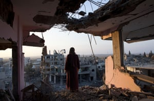 A Palestinian woman overlooks the destruction in Shujayea at dawn. A 72 hour cease fire came to an end without a longer term agreement. Rockets fired by Palestinian militants hit Israel and Israel resumed its air strikes.