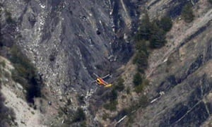 A helicopter flies over the crash scene where debris from the Germanwings A320 plane can be seen