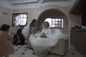 Palestinian bride Anaan El Harazen, 24, sits in the damaged salon of her family's home as she waits to pose for pictures with family members before her groom comes to take her away for their wedding