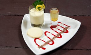 The lemon posset on a triangular white plate with a decorative red swirl