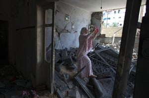 11 August 2014 Palestinian Hadil Amar, 21, uses her tablet to photograph herself with the damage to her family's home in Tel al Hawa in central Gaza.  The family fled their home late last night just before the cease fire after it was hit with a warning rocket by an Israeli drone just before it was targeted by Israeli war jets. Witnesses claim the home was hit twice. An Egyptian-brokered 72 hour cease-fire halting the Gaza war went into effect just after midnight