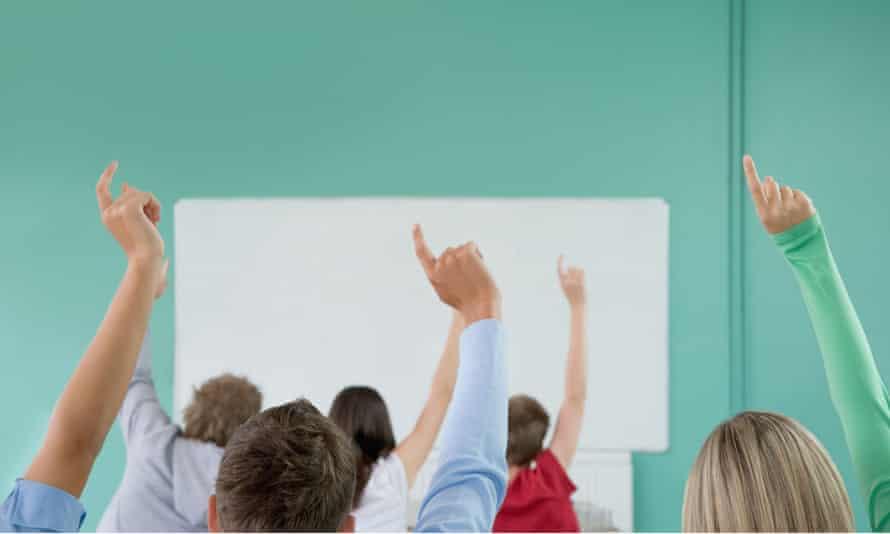 People raising hands in class