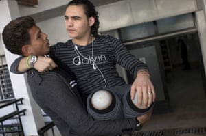 Palestinian Mustafa Majedah, 19, is carried by his friend Mohammed as they arrive for his rehabilitation session at the Artificial Limbs and Polio Center in Gaza City