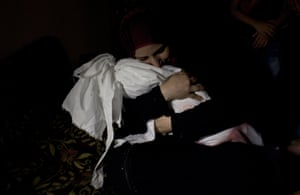 Netream Netzleam holds the body of her daughter Razel, 1, who medics said died from injuries sustained in an Israeli air strike the previous day, at her funeral in Rafah in the southern Gaza Strip