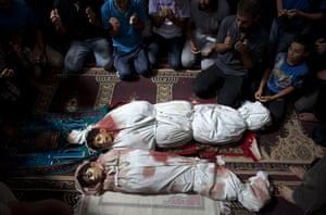 Family members pray in the mosque in Sajeria, Gaza by the bodies of Amir, 15, Mustafa Arief and Mohammed during their funeral in Sajeria, Gaza