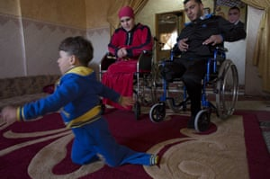 Wounded Wael al-Namlah, 26, and his wife Asraah as their three year-old son Sharif  crawls on the carpet at their home in Rafa, Gaza