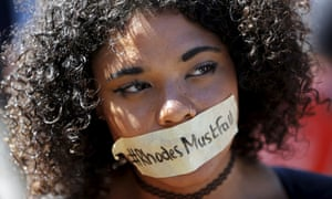 A student wears a sticker calling for the removal of a statue of Cecil John Rhodes from the campus of the University of Cape Town.