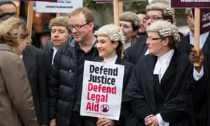 """lawyers, some in wigs, protest, including one holding a placard reading """"defend justice, defend legal aid"""""""