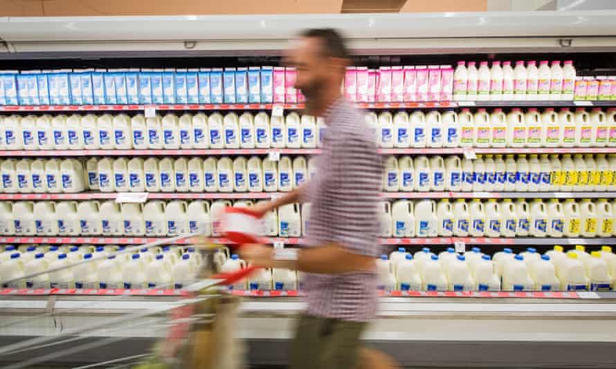 A shopper walks past bottles of milk
