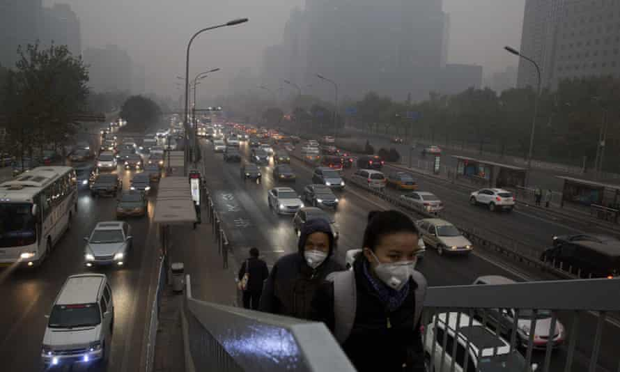 Pedestrians wear masks against the pollution as they cross an overhead bridge over a busy highway in Beijing, China, on  November 29, 2014.