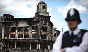 A policeman in front of a burnt-out shop in Tottenham after riots sparked by Mark Duggan's death