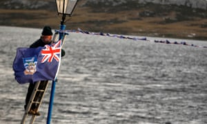 An islander hangs a Falklands flag from a lamppost in Port Stanley