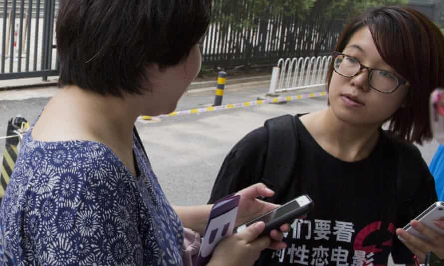 Wei Tingting, right, waits outside a court in Beijing last year. Wei is one of five female activists detained for planning to put up anti-sexual harassment posters.
